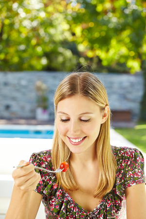 Happy woman is eating salad with fork in the garden