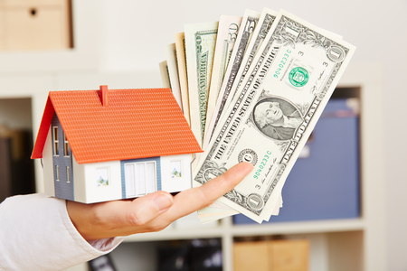 Female hand holds dollars and a small house as a symbol for mortgage lending