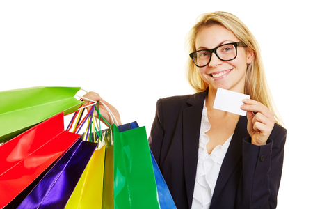 Smiling woman with many colorful shopping bags shows credit card