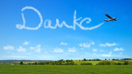 """L'avion écrit le mot allemand """"Danke"""" (merci) en écriture manuscrite au ciel en guise de remerciement Banque d'images"""