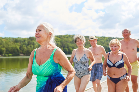 Vital senior woman and friends go on summer vacation on the lake while bathing