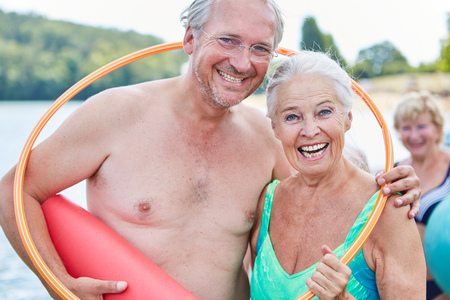 Laughing vital senior couple in summer vacation with a hoop and yoga mat