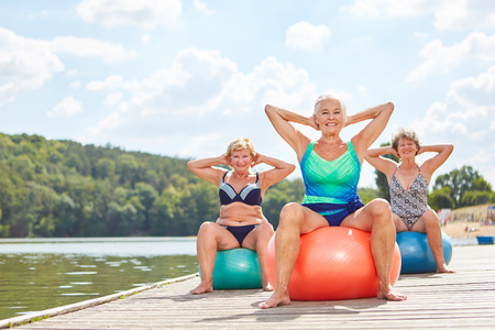 Group of senior women with stability ball doing back exercises at the lake in summer