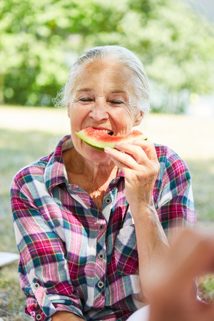 Hungry senior woman is eating a watermelon in the park on a trip in the summer Reklamní fotografie
