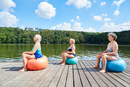 Group of senior women at rehabilitation Back training with gym ball at the lake in summer