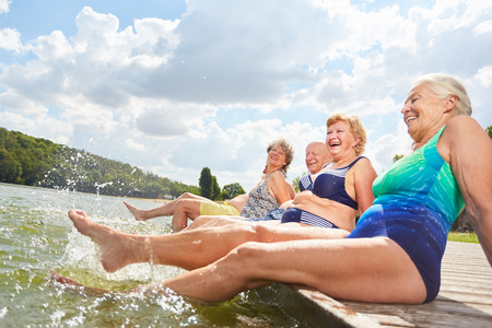 Active seniors splashing with their feet in the water during a summer vacation at the bathing lake Фото со стока