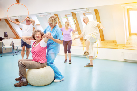 Senior citizens do back training as a course in a nursing home with a physiotherapist Reklamní fotografie - 119655076