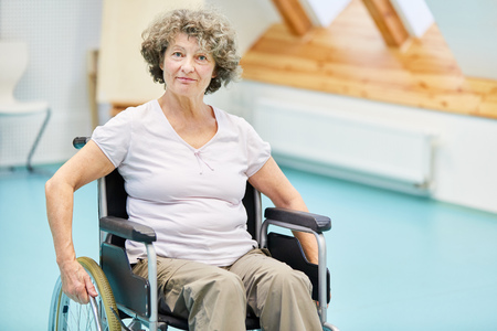 Senior woman in wheelchair after a stroke recovers at the rehab clinic