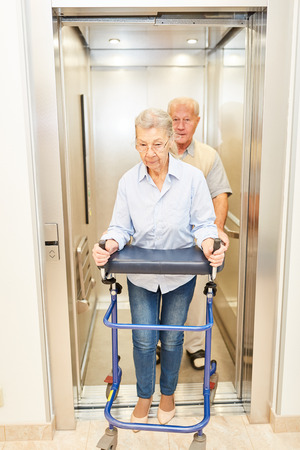 Two seniors with walkers in a lift in a rehab clinic or nursing home Stock Photo