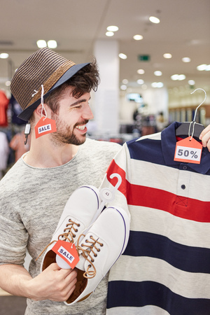 Young man as a customer shopping for clothes with 50% off discount