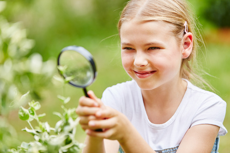Girl researches with magnifying glass in garden and explores nature with curiosity Stock Photo