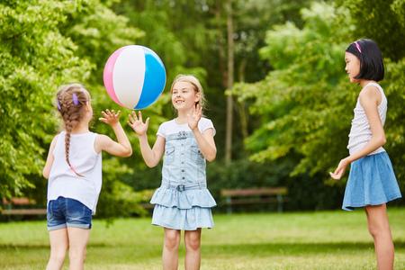 Drei Mädchen spielen Fangen und Werfen zusammen mit Ball Standard-Bild