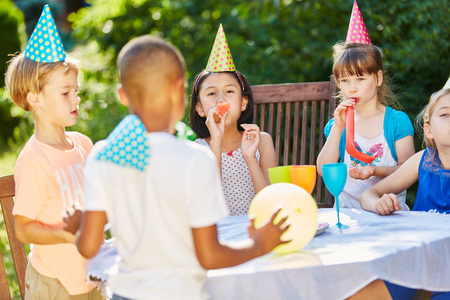 Children in international kindergarden celebrate together at party in summer Stock Photo