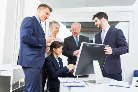 Business people in front of computer monitor videoconferencing with team Archivio Fotografico