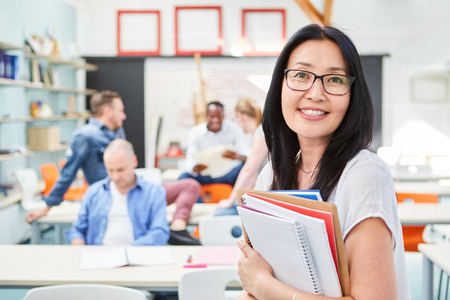 Junge Asiatin als Dozentin mit Unterlagen in einem Seminar der Universität