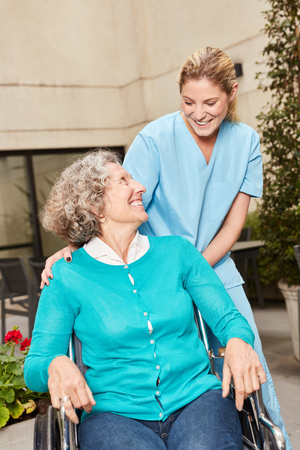 Senior in wheelchair and caregiver in rehab clinic or nursing home Stock Photo