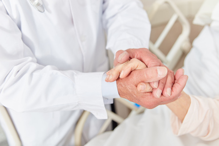 Caring doctor holds a patients hand in the hospital as comfort