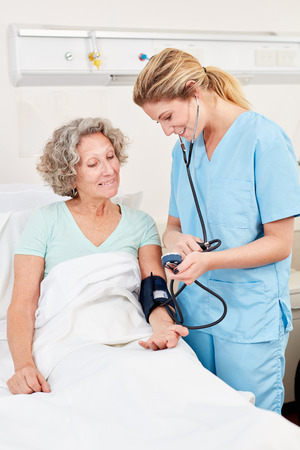 Nurse measuring blood pressure in a senior patient