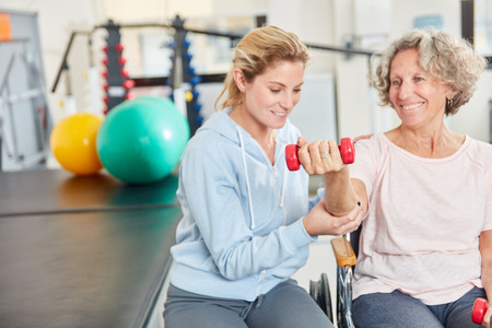 Physiotherapist supports senior woman with dumbbell training in rehab 版權商用圖片