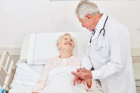 Caring doctor in conversation with a bedridden senior citizen in the hospital
