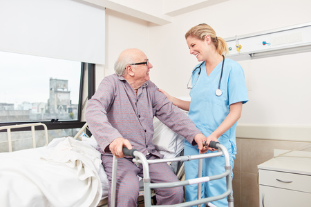 Nurse cares about disabled senior man with walker Stock Photo