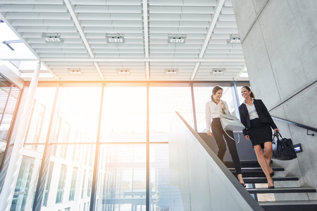Two business women talk on the stairs to the office with each other Banque d'images - 120905442