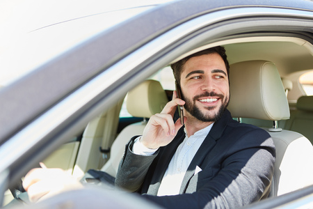 Young businessman is phoning with smartphone while driving a car Banque d'images - 120905447