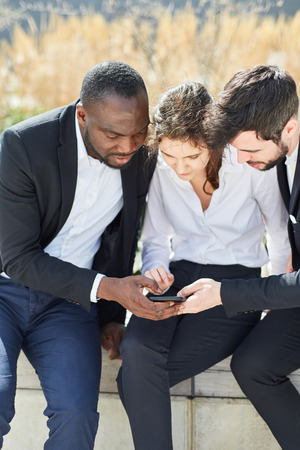 Three business people reading or writing a text message together on a smartphone Banque d'images - 120905455