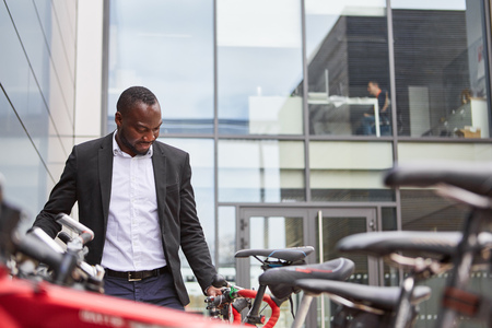 African businessman with bicycle in front of the corporation or office building Banque d'images - 120905457