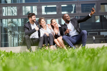 Happy business team makes selfie with smartphone in front of the office in summer Banque d'images - 120905458