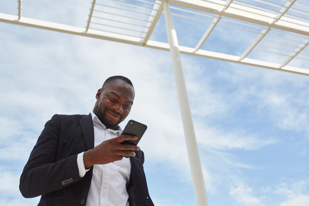 African businessman is happy about text message on the smartphone Banque d'images - 121134340