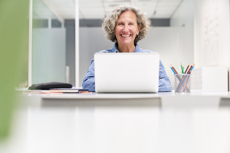 Smiling senior woman is working with laptop computer in co-working workplace Banque d'images - 121134637