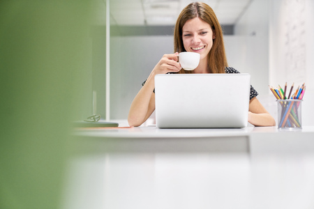 Young business woman on laptop computer is drinking a cup of coffee for refreshment Banque d'images - 121134717