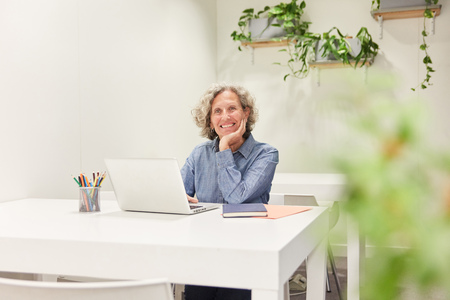 Senior as a competent manager at the laptop computer in the coworking office Banque d'images - 121134720