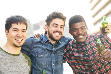 Young multicultural friends celebrate with beer at a party or at the end of the day Banque d'images - 121134724