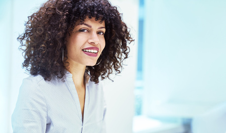 Young businesswoman with curly hair in the office of a start-up company Banque d'images - 121134726