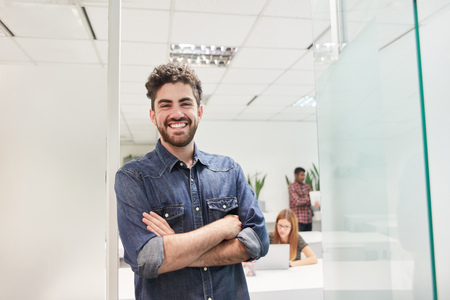 Young man as a self-confident start-up business founder in front of the coworking office Banque d'images - 121134737