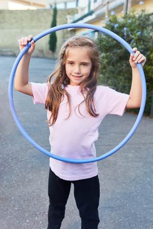 Happy girl is doing an exercise with the tire in gym class