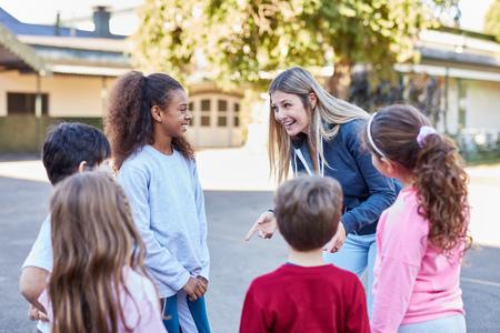 Assistenti e bambini in educazione fisica al campo o nel tempo libero dei bambini