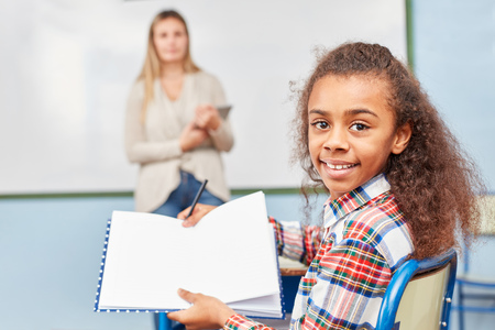 Schoolgirl proudly shows her notebook with the homework in elementary school