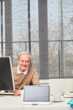 Senior businessman at his office working with computer  Archivio Fotografico