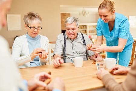Pflegeheimpflege für Senioren beim Kaffeetrinken und Spielen im Altersheim