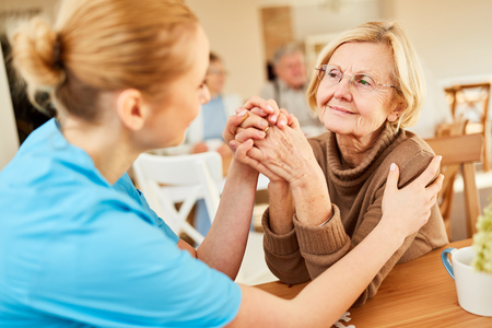 Demented or ill senior woman is being comforted by a geriatric nurse in the nursing home