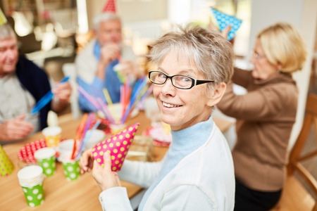 Senior woman in retirement home celebrates carnival or birthday together with friends