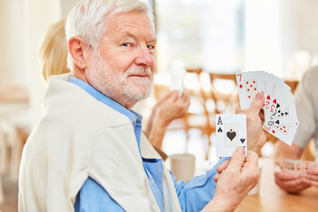 Senior man shows an ace when playing cards with friends in retirement home