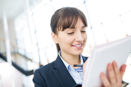 Closeup of businesswoman smiling while writing on document in office