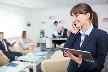 Smiling young businesswoman talking on smartphone while holding digital tablet in meeting room at office