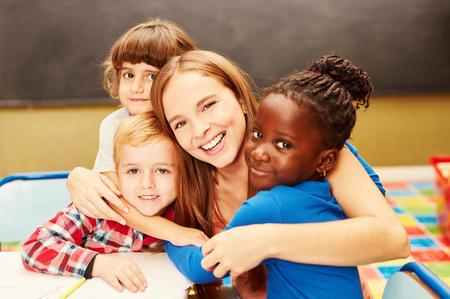 Los niños felices abrazan a su niñera en el cuidado infantil
