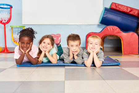 Four multicultural kids as friends in the gym in kindergarten or preschool Stock Photo