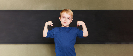 Proud strong student shows his muscles in front of a blackboard in elementary school